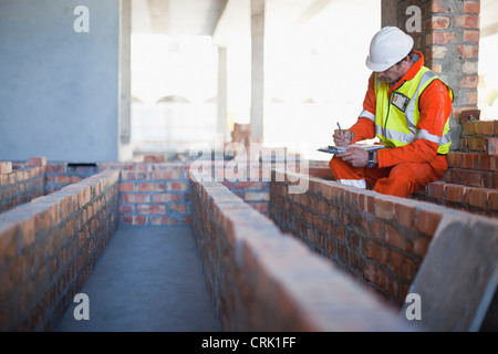 Worker writing on clipboard on site - Stock Photo