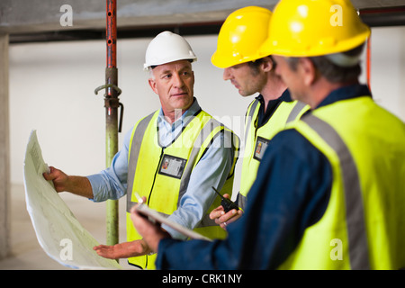 Workers reading blueprints on site - Stock Photo