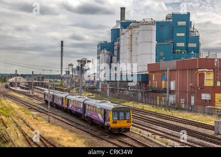 Warrington Bank Quay station with the Unilever factory behind. - Stock Photo