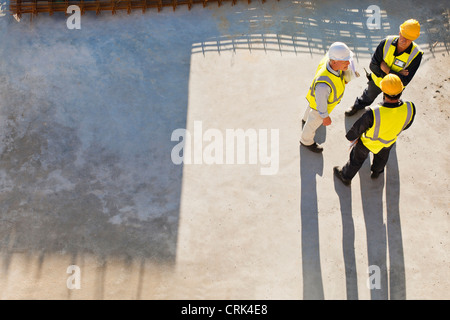 Workers casting shadows on site - Stock Photo