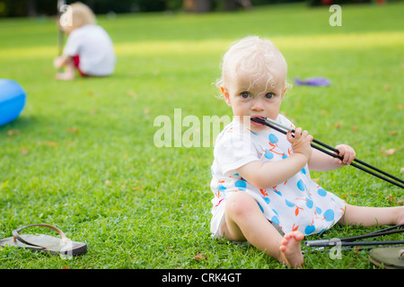 Baby girl chewing on toys in backyard - Stock Photo