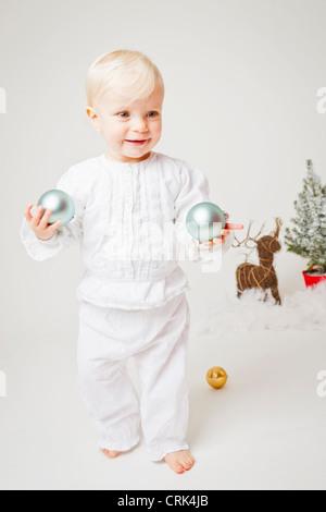 Baby girl holding Christmas ornaments - Stock Photo