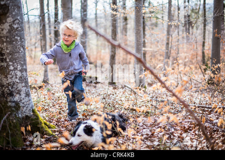 Boy and dog exploring in forest - Stock Photo