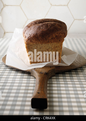 Freshly baked bread on wooden paddle - Stock Photo