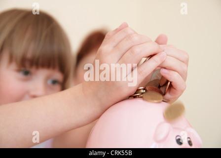 Girl putting money in piggy bank - Stock Photo