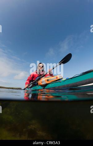 Man kayaking on still lake - Stock Photo