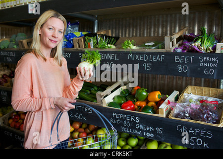 Woman buying produce in store - Stock Photo