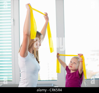 Trainer working with girl in gym - Stock Photo