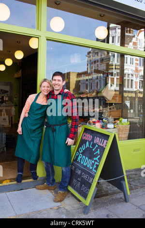 Smiling grocers standing outside store - Stock Photo