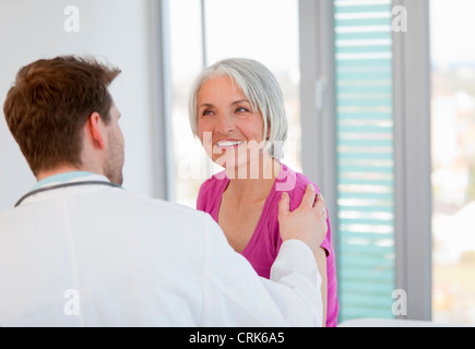 Doctor talking to woman in office - Stock Photo