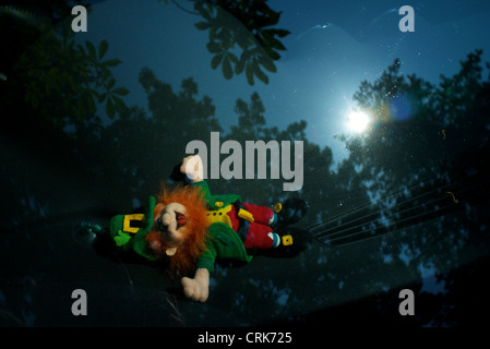 © Paul Treacy 2012. Sunbathing leprechaun toy on car dashboard in Sydenham, London. - Stock Photo