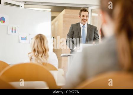Businessman hosting seminar in office - Stock Photo