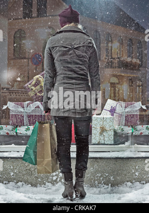 Woman carrying shopping bags in snow - Stock Photo