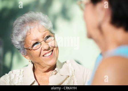 Active retirement, two elderly female friends talking on bench in public park - Stock Photo