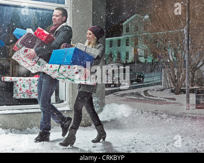 Couple with Christmas gifts in snow - Stock Photo