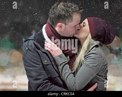 Couple kissing in snow at night Stock Photo