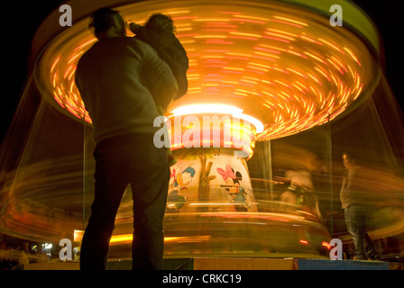 People looking at a Merry-go-round - Stock Photo