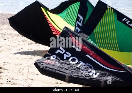 Flexifol power kite resting on a beach - Stock Photo