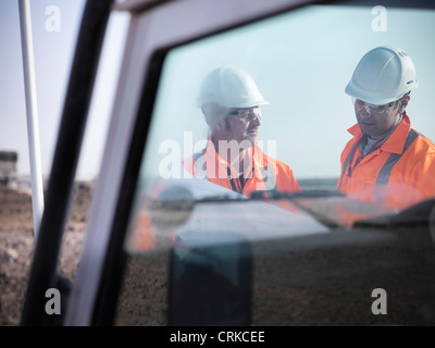 Workers reading blueprints at coal mine - Stock Photo