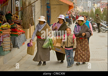 A group of local Chinese Tibetan women dressed in traditional clothes shopping in the center of Xiahe. - Stock Photo