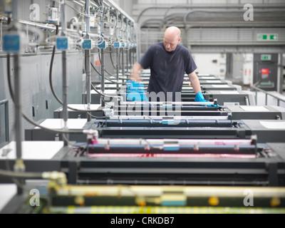 Printer inking printing press in shop - Stock Photo