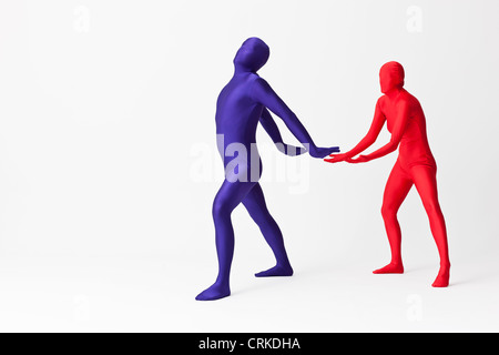 Couple in bodysuits with invisible globe - Stock Photo
