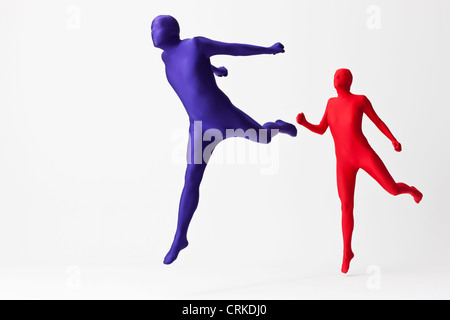 Couple in bodysuits jumping - Stock Photo