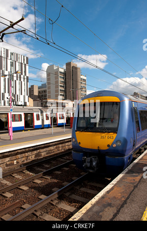 Train in C2C livery and a London Underground train waiting at a railway station in England. - Stock Photo