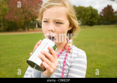 Girl playing with tin can telephone - Stock Photo