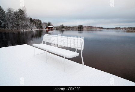 Snowy bench on pier at river Nokisenkoski  , Finland - Stock Photo
