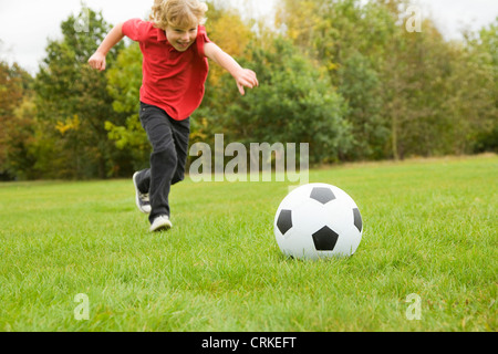 Boy playing with soccer ball in field - Stock Photo