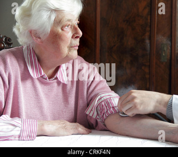 Older woman having pulse checked - Stock Photo