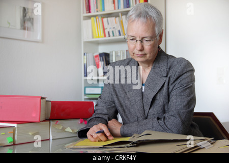 Lawyer reading notes in office - Stock Photo