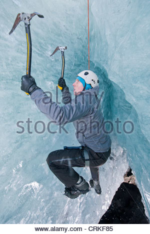 Climber climbing out of ice cave - Stock Photo