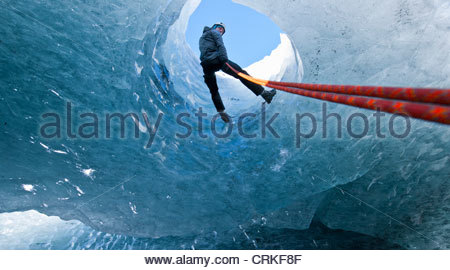 Climber abseiling into ice cave - Stock Photo