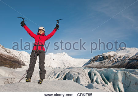 Climber cheering on top of glacier - Stock Photo