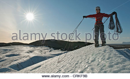 Climber coiling rope on glacier - Stock Photo