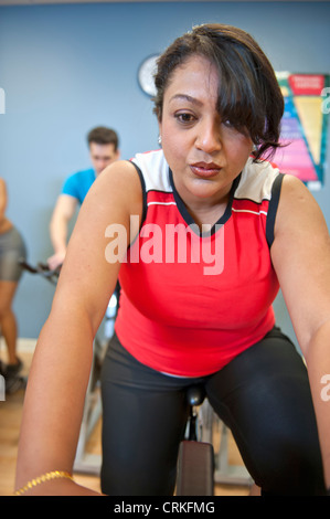 Woman using spin machine in gym - Stock Photo