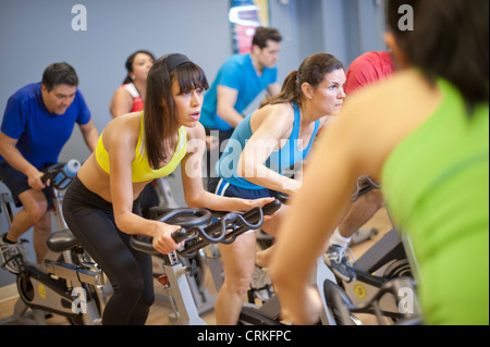 People using spin machines in gym - Stock Photo