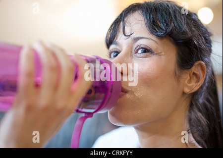 Woman drinking water bottle in gym - Stock Photo