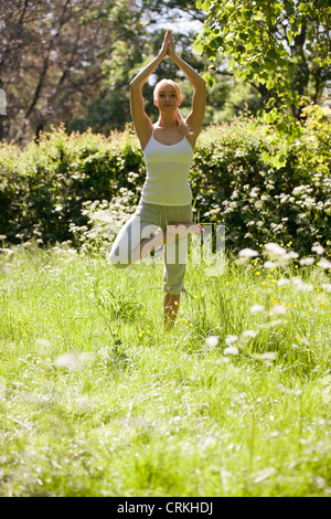 A young woman practicing yoga outside, standing in tree pose (Vriksasana) - Stock Photo