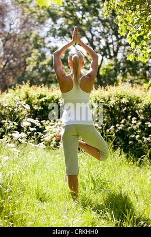 A young woman practicing yoga outside, standing in tree pose (Vriksasana) , back view - Stock Photo