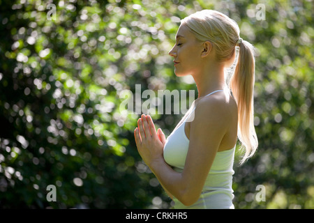 A young woman practicing yoga outside, hands in prayer position - Stock Photo