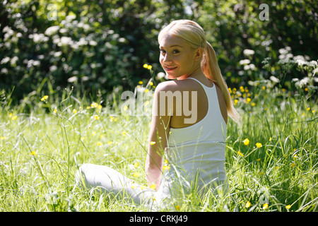 A young woman sitting amongst spring flowers, smiling - Stock Photo