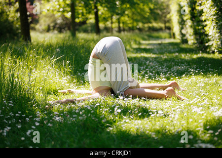 A young woman practicing yoga outside, ear pressure pose - Stock Photo