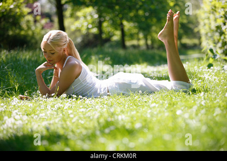 A young woman laying in the grass looking thoughtful - Stock Photo