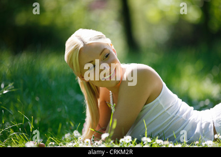 A young woman laying in the grass smiling - Stock Photo