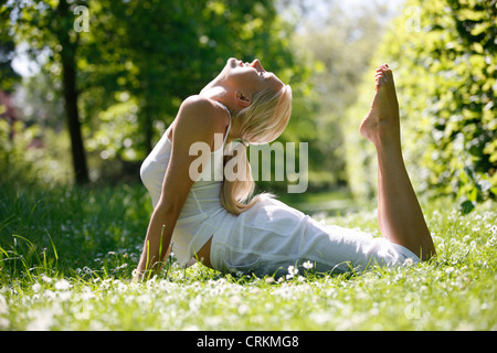 A young woman practicing yoga outside - Stock Photo