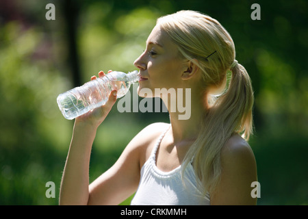 A young blonde drinking a bottle of water, close up - Stock Photo