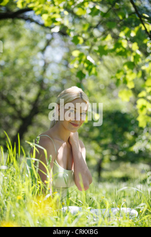 A young blond woman sitting in the grass, smiling to camera - Stock Photo